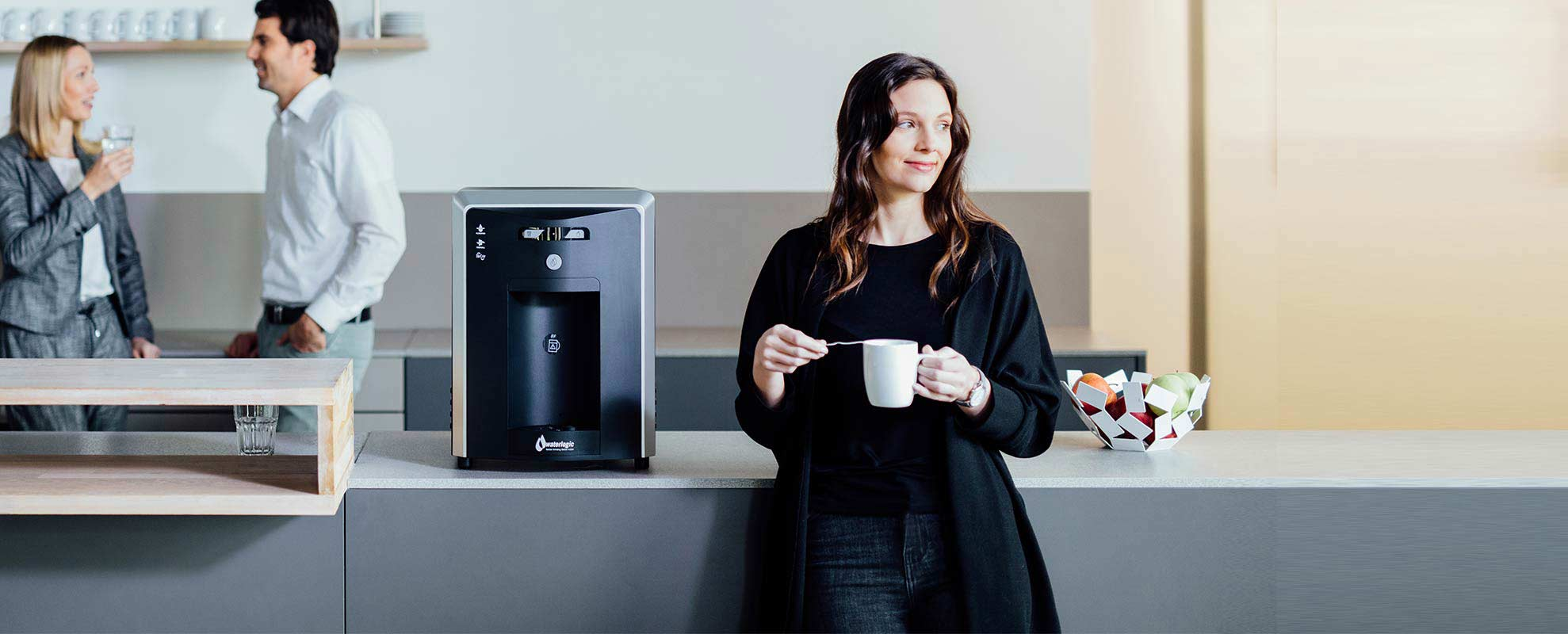 lady drinking a cup of tea standing next to a bottle less watercooler